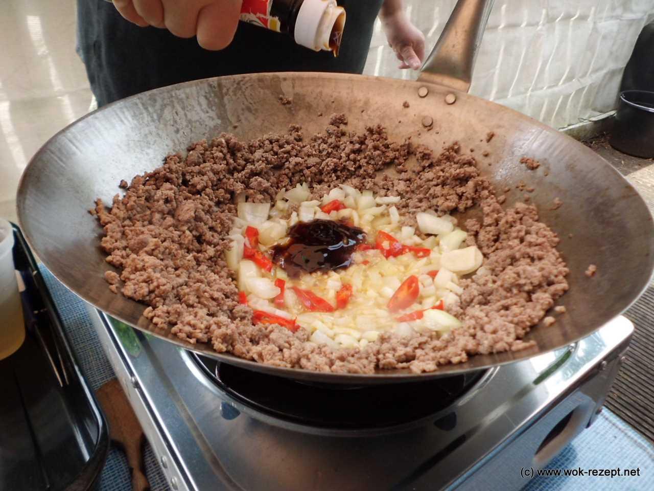 Austernsauce, Zwiebeln, Knoblauch und Chili unterheben
